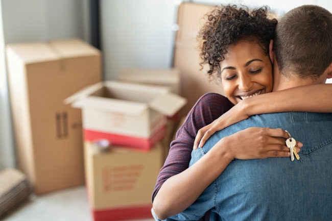 Couple embrace after moving into new home.