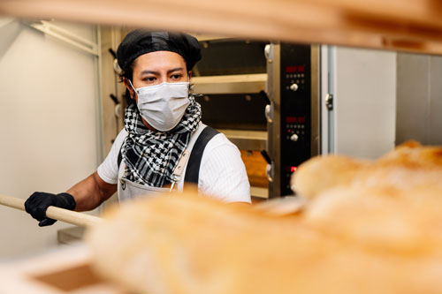 Baker moving bread out of oven